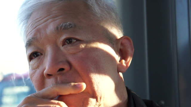 Asian senior man thinking in tram while morning sun hitting his face video