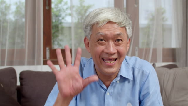 自宅でアジアのシニア男性のビデオ通話。自宅のリビングルームでソファに横たわっている間、携帯電話のビデオ通話を使用してアジアの高齢中国人男性。カメラを見て - テレビ会議 日本人点の映像素材/bロール