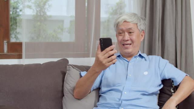 自宅でアジアのシニア男性のビデオ通話。携帯電話のビデオ通話を使用してアジアの高齢の中国の男性は、自宅のコンセプトでリビングルームでソファに横たわっている間、家族の孫の子供� - テレビ会議 日本人点の映像素材/bロール