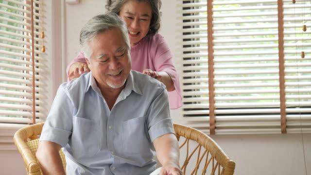 シニア男性妻自宅でマッサージをしました。シニアのライフ スタイルの家族概念。 - 老夫婦点の映像素材/bロール
