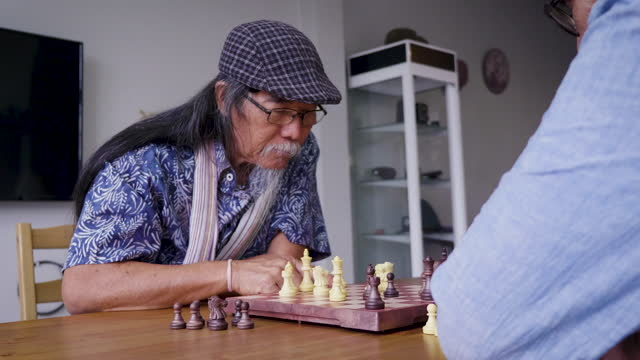 Asian senior men friends playing chess in living room at home, Active senior people concept