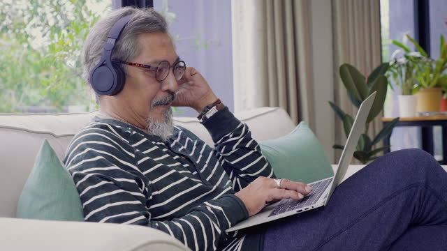 Asian senior men listening to music with headphone and using laptop computer while setting on sofa in living room at home