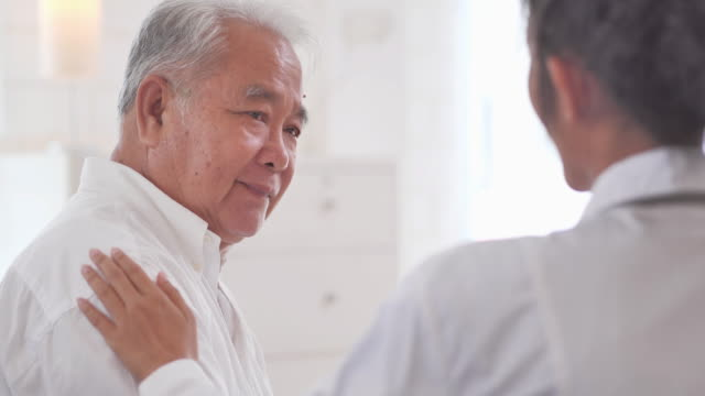 Asian senior old man listening to young black female nurse doctor in consultation to his older male patient at home.Medical,Caretaking,Care,Retirement,Volunteer,Charity,Education,Nursing home,Caregivers at Home,Medicine and health care - vídeo