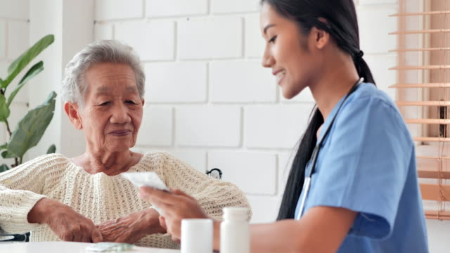 Asian senior old woman listening to young black female nurse doctor explaining medicine to her older female patient at home.Medical,Caretaking,Care,Retirement,Volunteer,Charity,Education,Nursing home,Caregivers at Home,Medicine and health care video