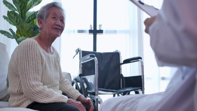 若い女性看護師の医師と話しているアジアの先輩女性は、自宅での検診で患者を助けます。高齢のおばあちゃんは、サポートを与える介護者、医療、介護、高齢者ケア、退職、ボランティア� - 介護点の映像素材/bロール