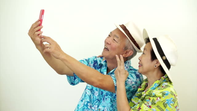 Asian senior tourist couple taking a selfie on holiday vacation video