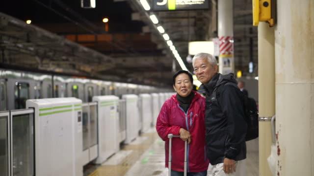 asian senior travel backpack in japanese train for holiday - cultura coreana video stock e b–roll