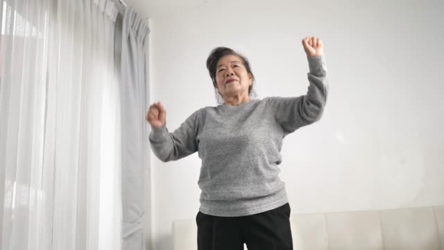 stockvideo's en b-roll-footage met aziatische hogere vrouw die oefening doet en thuis danst, blijf huis levensstijlconcept. slow motion. - dansstudio
