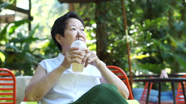 Asian senior woman drinking coffee happily in green lush nature coffee shop