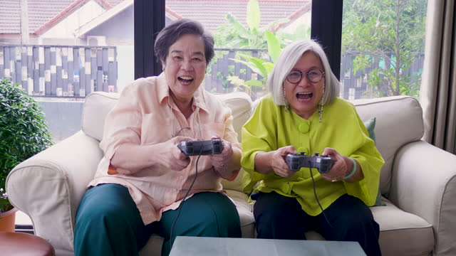 Asian senior woman friends enjoy playing video games together in living room at home