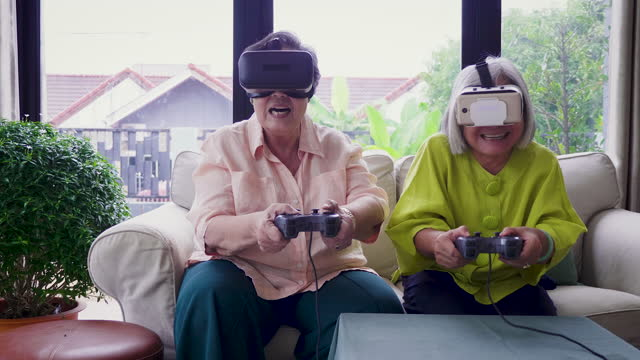 Asian senior woman friends enjoy playing video games with virtual reality glasses together in living room at home