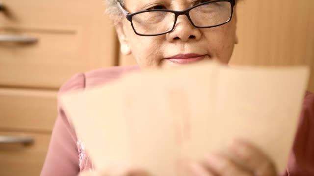 Asian Senior Woman Looking Old Photo