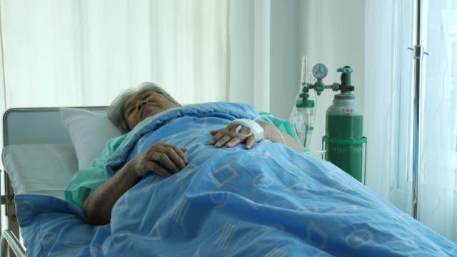 Asian senior woman patient , lying down on bed video