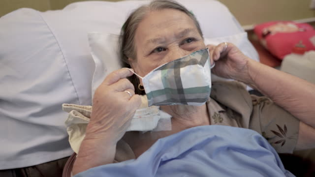 vídeos de stock, filmes e b-roll de paciente asiática idosa usando máscara facial médica no hospital - diálise