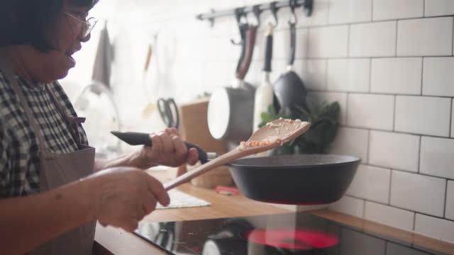 Asian senior woman preparing food.