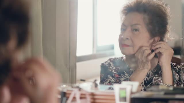 senior asiatin setzen ihre ohrringe und make-up - ohrring stock-videos und b-roll-filmmaterial
