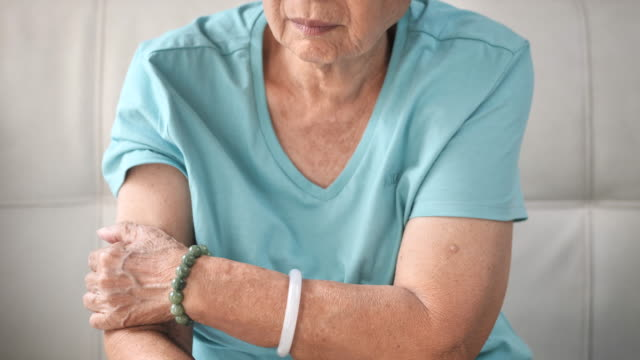 Asian senior woman scratching her arm, health care concept and slow