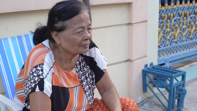 Asian senior woman sitting alone outside the house Asian senior woman sitting alone outside the house park bench stock videos & royalty-free footage