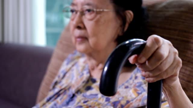 asian senior woman sitting in chair holding walking stick - människokroppsdel bildbanksvideor och videomaterial från bakom kulisserna