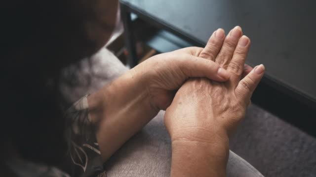 asya kıdemli kadın oturan üzerinde bir kanepe sahip bir el pain. masaj üzerinde ona el - hayvan eklemi stok videoları ve detay görüntü çekimi