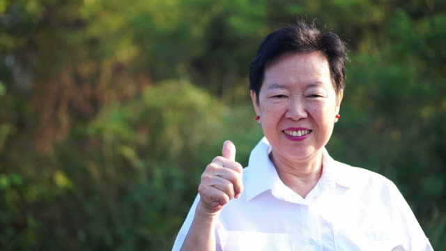 asian senior woman thumb up and smiling with green nature background - thank you stock videos and b-roll footage