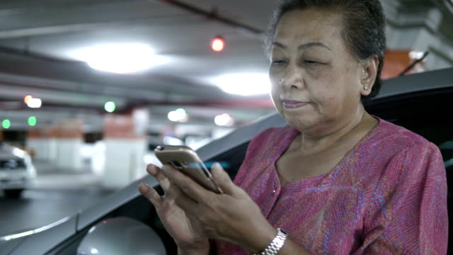 asian senior woman using smart phone at the car park - 60 69 anni video stock e b–roll