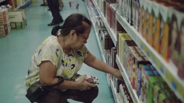 Asian senior woman using smartphone in supermarket video