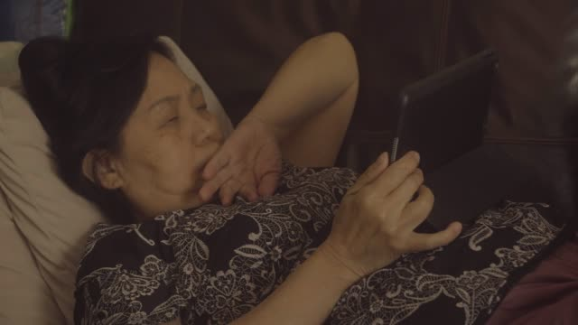 Asian senior woman using tablet watch online movie.