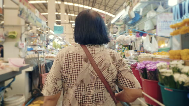 asian senior woman walking and shopping in at farmers market. bangkok, thailand. - agricoltrice video stock e b–roll