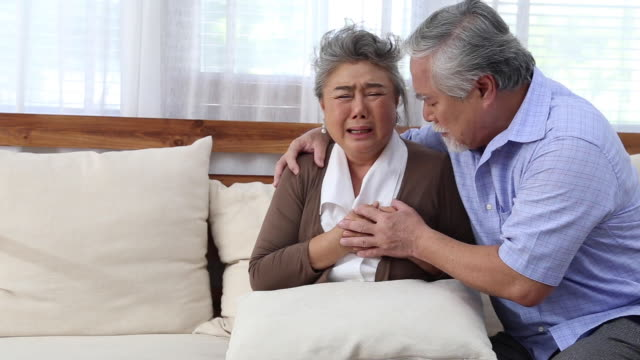 asian senior woman with pain on heart on sofa in living room and take care by her husband, health problem and feeling sick - klatka piersiowa tułów filmów i materiałów b-roll