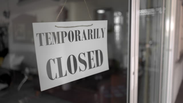 Asian senior women changing open to temporarity closed sign on shop door