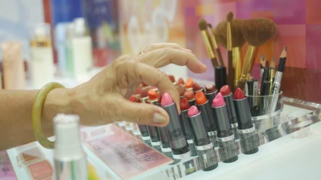 Asian senior women testing lipstick at store video