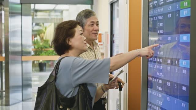 アジアの高齢者が到着出発ボードの時間を確認 - 乗客点の映像素材/bロール