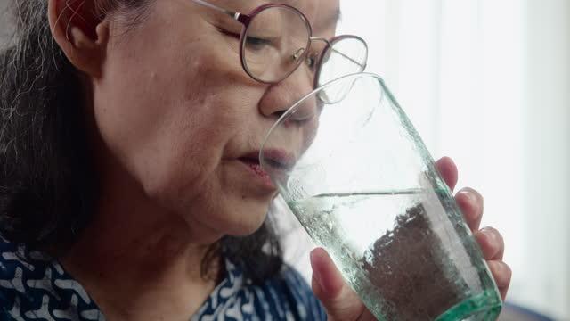 Asian Seniors women taking medication.