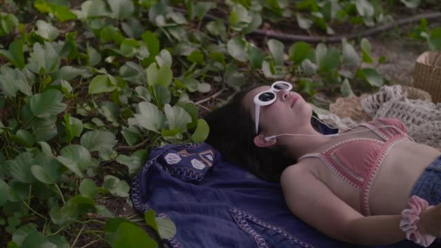 Asian sexy girl in bikini Lying on the beach enjoying inserting earphones.