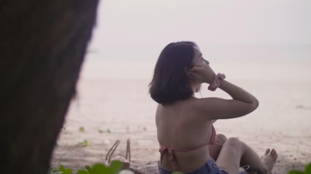 Asian sexy girl in bikini on the beach enjoying inserting earphones.
