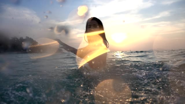 asian sexy girl in bikini with wet hair and lips having fun splashing in the sunset at sea - chlapać filmów i materiałów b-roll