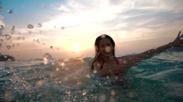 vídeos de stock e filmes b-roll de asian sexy girl in bikini with wet hair and lips having fun splashing in the sunset at sea - water splash