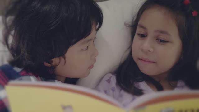asian sibling reading story book at night. - personaggio fantastico video stock e b–roll
