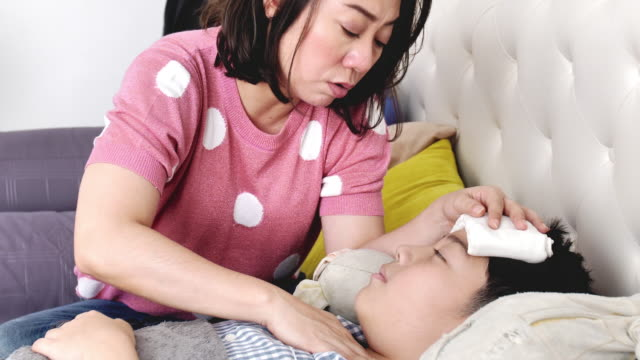 Asian Sick boy, lying in bed, mother checking his temperature, Slow motion of mother and son at home.
