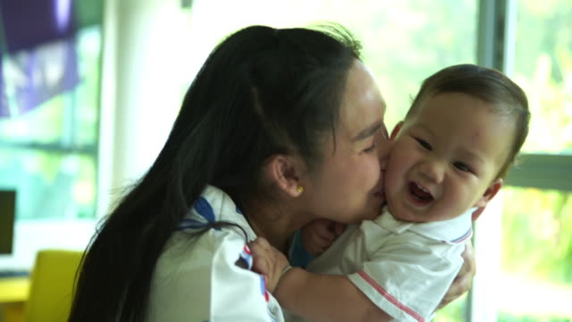 Asian single mom playing and kissing with her baby boy - vídeo