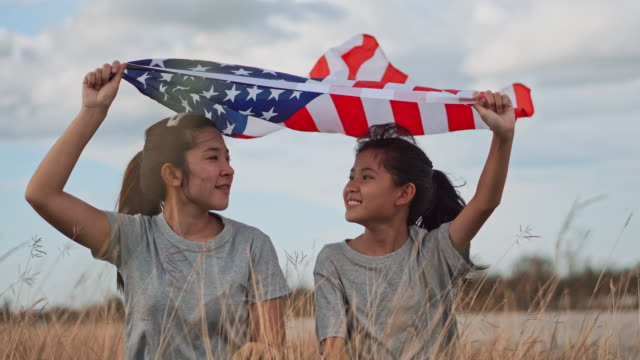 Asian Sisters happy and fun with American flag USA celebrate 4th of July Asian Sisters happy and fun with American flag USA celebrate 4th of July happy 4th of july videos stock videos & royalty-free footage
