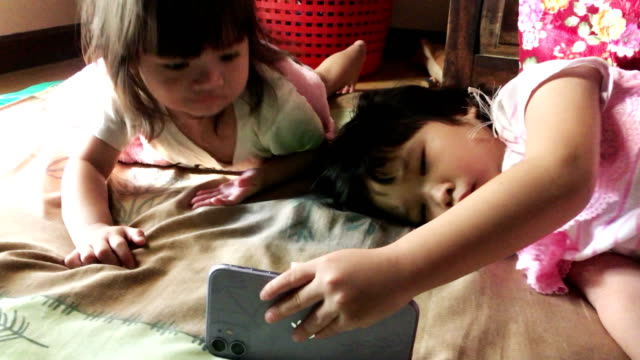 Asian sisters sharing mobile phone together at home video