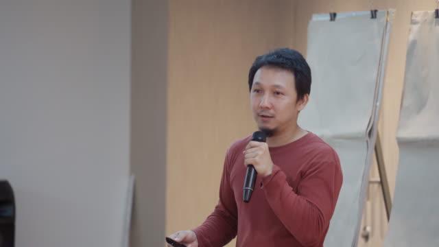 vídeos de stock e filmes b-roll de asian speaker with casual suit presenting in front of the seminar meeting room or conference hall - orador público