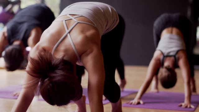 Asian sport woman and caucasian white training yoga in yoga studio coaching by trainer,open light from nature.Healthy,city life style concept.slow motion footage.