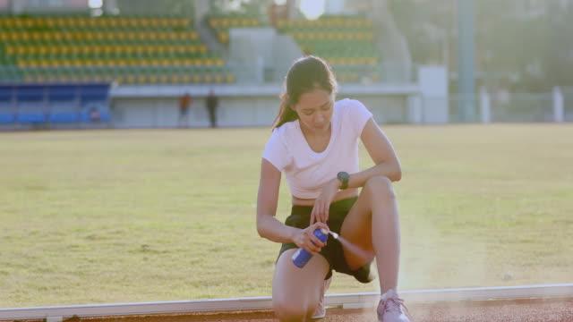 vídeos de stock, filmes e b-roll de mulheres da asian sports usando spray congelante para tratar joelho e perna de mulheres atletas feridas após corrida - relevo