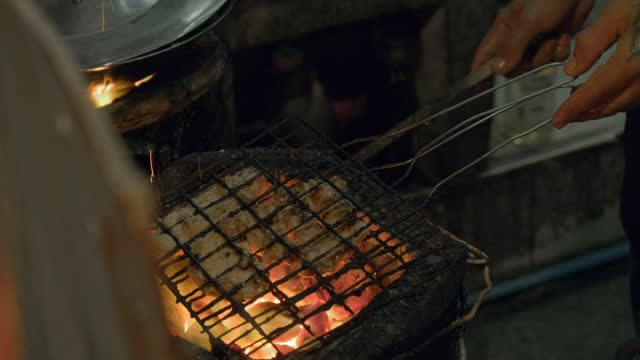 Asian street food on Thailand market. Chef is grilling meat.