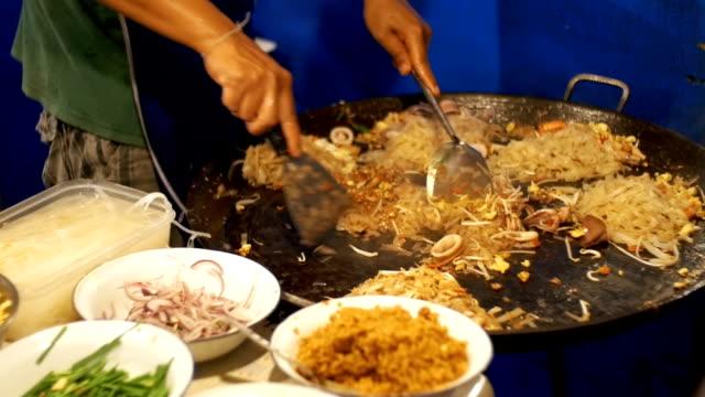 Asian Street Food. Meeresfrüchte, Nudeln Reis mit Ei in einer großen Pfanne kochen. Slow-Motion. Thailand – Video