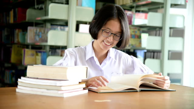 Asian student girl reading book in public library video