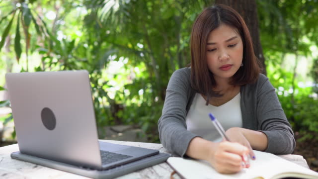 Asian student woman studying outdoor using laptop and writing notebook in park of university